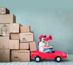 Enfant dans une voiturette près de cartons